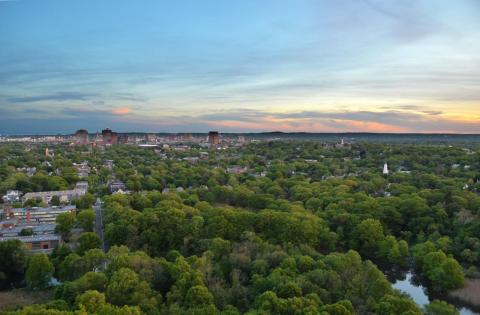 Downtown New Haven and the East Rock neighborhood at sunset, as viewed from above Orange street. Photo by Ethan Bernard.