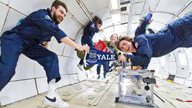 Tyler Krebs and Paul Meuser holding a Yale pennant while on G-Force One (Photo by Steve Boxall, ZERO-G)